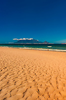 View of Cape Town and Table Mountain and Lion's Head Peak from the beach at Bloubergstrand, South Africa.