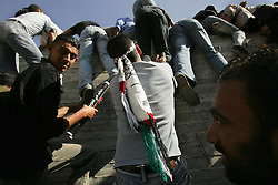 Palestinians rush the Mukataa, the headquarters of the Palestinian National Authority, to get a glimpse of Yasser Arafat as he is buried, Ramallah, Palestinian Territories, Nov. 12, 2004. Arafat died in a Paris hospital at the age of 75.