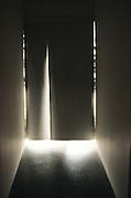 Abstract view of hall with light shining behind a dark curtain