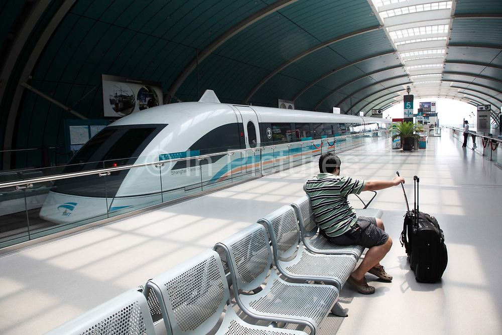 Passengers wait to board the Transrapid magnetic levitation (maglev) train at its station in Shanghai, China on 20 June 2009. A often criticized grand infrastructure pet project of the Shanghai government, the Shanghai maglev line is the only operational commercial one in the world, reaching speeds of up to 430KPH during its 33 kilometer journey connecting the City's Pudong Airport with the Longyang Road subway station on the edge of the city.