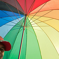 Participant of the Gay Pride March smiles under a rainbow colored umbrella in Budapest, Hungary on June 18, 2011. ATTILA VOLGYI