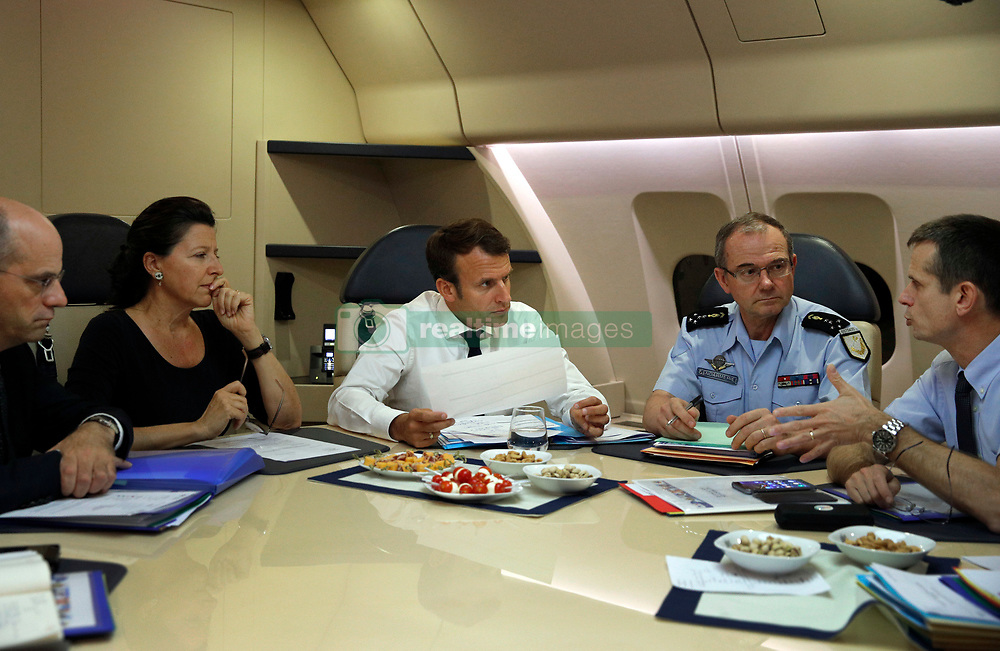 France's President Emmanuel Macron, center, confers with officials aboard the presidential plane en route to Guadeloupe Island, the first step of his visit to French Caribbean islands, Tuesday, Sept. 12, 2017. Seated at the table from left are French Education Minister Jean-Michel Blanquer, French Minister for Solidarity and Health Agnes Buzyn, Director General of the Gendarmerie Nationale, Richard Lizurey, director of the rescue service (Securite Civile), Jacques Witkowski. Photo by Christophe Ena/Pool/ABACAPRESS.COM