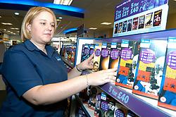 Young woman working in Blockbuster video rental shop; stacking shelves; Merseyside; UK