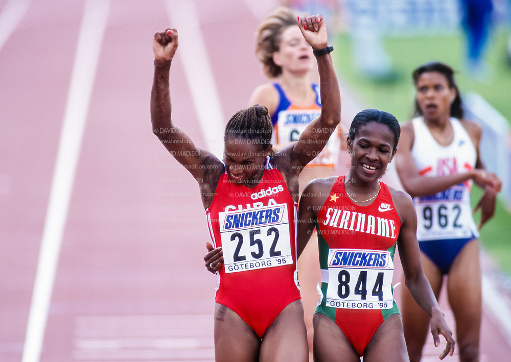 GOTHENBURG, SWEDEN -  AUGUST 13:  Ana Fidelia Quirot #252 of Cuba celebrates her victory in the Women's 800 meter event during the 1995 IAAF World Championships held on August 13, 1995 at Ullevi Stadium in Gothenburg, Sweden.   Also visible is Letitia Vriesde #844 of Surinam, the silver medalist in the event; and Meredith Rainey-Valmon #962 of the USA.  (Photo by David Madison/Getty Images)