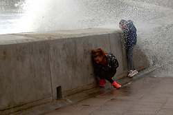 © Licensed to London News Pictures. 25/08/2020. Porthcawl, Bridgend, Wales, UK. Children enjoy the wind and spray as Storm Francis batters the small Welsh seaside resort of Porthcawl in Bridgend, UK. with severe gale force winds and massive waves. Photo credit: Graham M. Lawrence/LNP