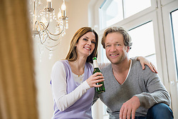 Smiling couple holding bottle of beer
