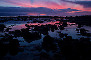A colorful sunset is reflected in the calm water at Sharks Cove on Oahu's North Shore, Hawaii