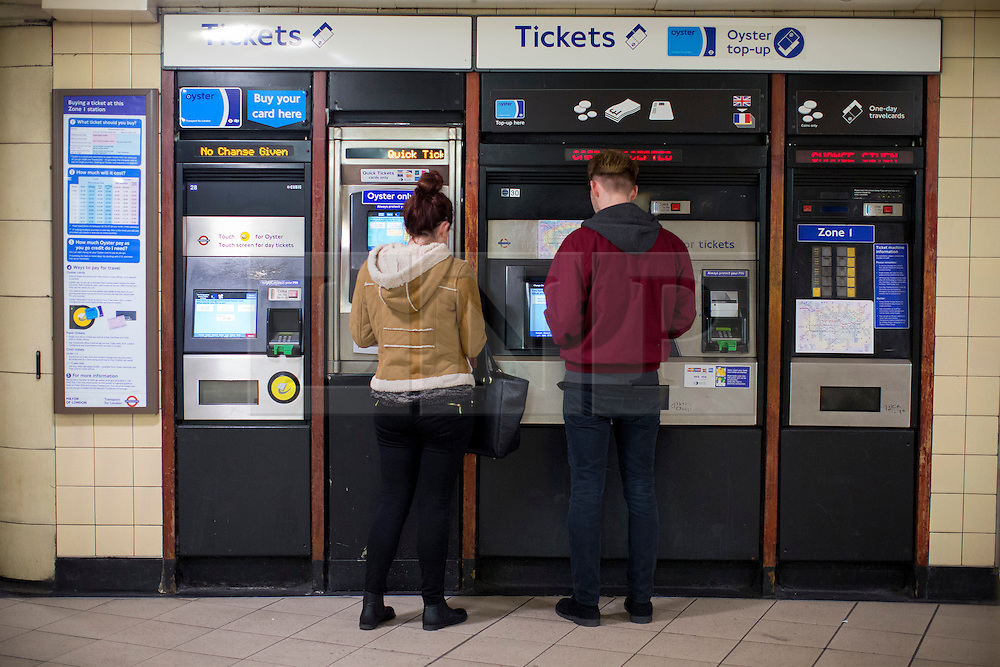 © licensed to London News Pictures. London, UK 21/11/2013. Tube passengers use ticket machines in central London on Thursday, November 21, 2013. TfL reveals the plans to shut London Tube ticket offices and cut 750 jobs by 2015 due to cuts of about £78m. Photo credit: Tolga Akmen/LNP