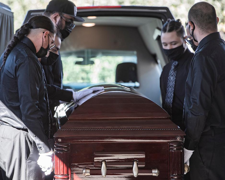 Pallbearers prepare to carry Carmelita Martinez' casket from the hearse at Pastor El Buen church in San Jose, Calif. on Feb. 3, 2021.