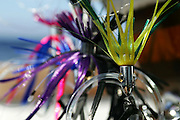 Colorful group of Ilslander lure heads on ballyhoo hook rigs hanging on fighting chair arm.