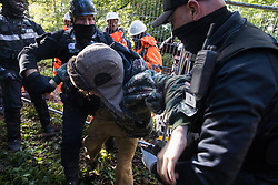 Aylesbury Vale, UK. 1st October, 2020. National Eviction Team bailiffs working on behalf of HS2 Ltd forcibly move an anti-HS2 activist away from a fence being constructed during evictions from a wildlife protection camp in the ancient woodland which inspired Roald Dahl's Fantastic Mr Fox at Jones' Hill Wood. Around 40 environmental activists and local residents, some of whom living in makeshift tree houses 60 feet above the ground, were present during the evictions at Jones' Hill Wood which had served as one of several protest camps set up along the route of the £106bn HS2 high-speed rail link in order to resist the controversial infrastructure project.
