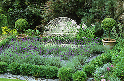 White iron seat and lavender maze with slate paths and box balls. Design: Alan Titchmarsh