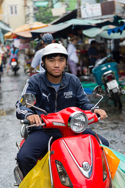 Young Vietnamese man on motor scooter rides through a market in Ho Chi Minh City.