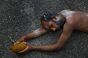 Exhausted Hindu devotees, who, carrying coconuts and covered with ash roll upon the London tarmac behind the chariot to participate in the annual Tamil chariot festival at the Murugan Temple in Highgate, London, England 17th July 2016. Thousands attend the colourful celebration as the temple's Goddess Amman (Tamil for Mother) is paraded on a beautifully decorated chariot pulled by the people through the streets around the temple, which brings to a close the four week Mahotsava festival.