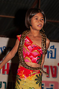 Young Thai girl with a python snake around her shoulders Photographed in Thailand