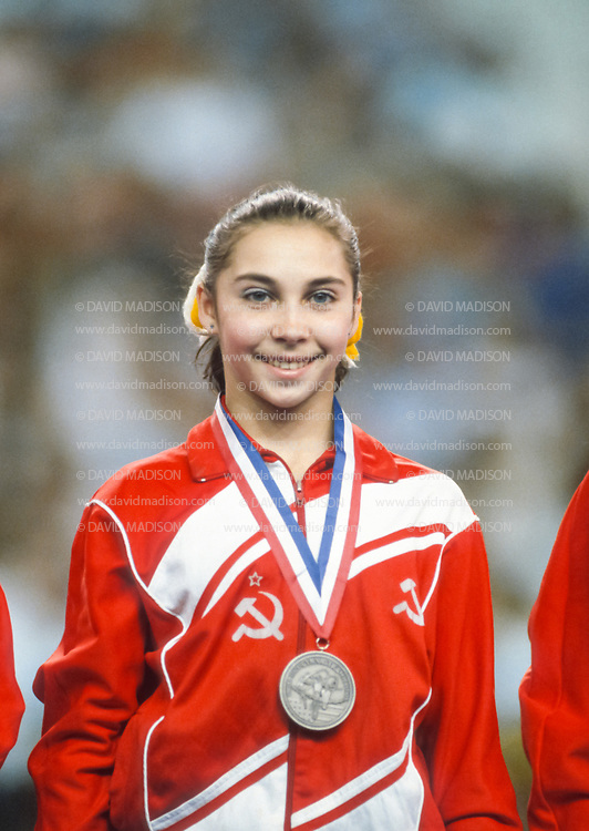 PHOENIX - APRIL 24:  Olga Strazheva of the USSR smiles after receiving a medal during a USA - USSR gymnastics meet on April 24, 1988  at the Arizona Veterans Memorial Coliseum in Phoenix, Arizona.  (Photo by David Madison/Getty Images)