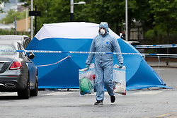 May 27, 2019 - London, London, UK - London, UK.  A Police forensic officer near a forensic tent at the crime scene in St Paul's Way, Mile End in Tower Hamlets, where a 23 year old man was stabbed multiple times yesterday, 26th May and died overnight in hospital. (Credit Image: © Vickie Flores/London News Pictures via ZUMA Wire)