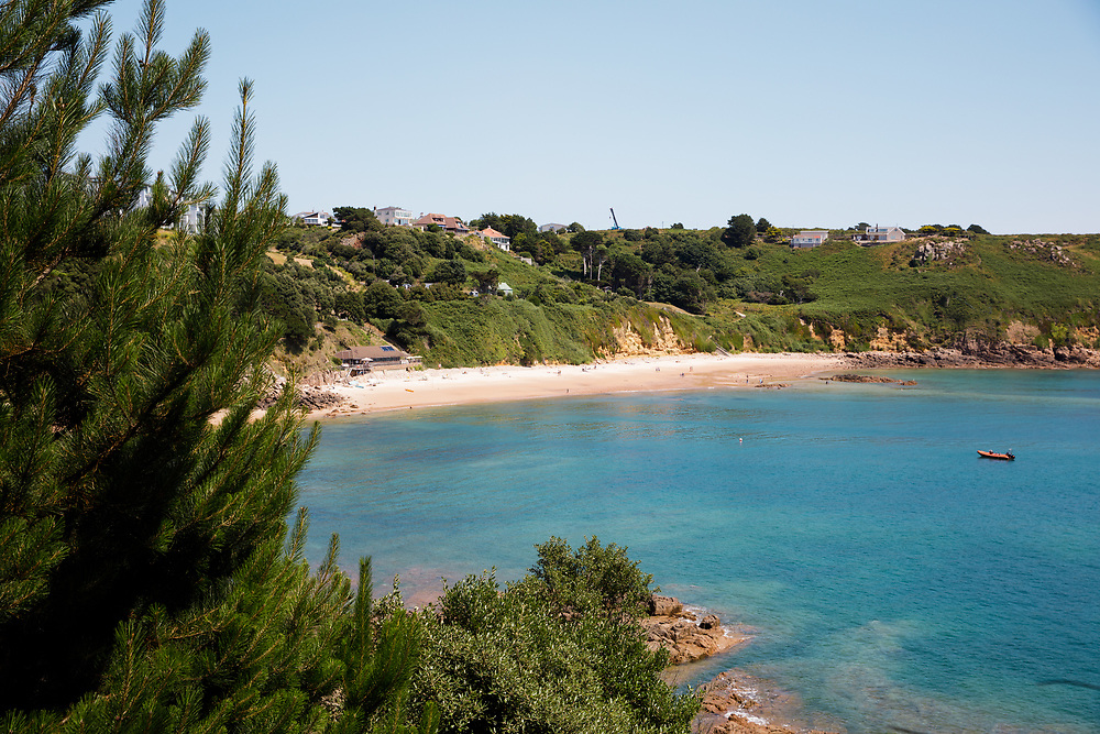 View across Portelet beach, with its calm blue waters, a popular beach with tourists and locals in Jersey, Channel Islands