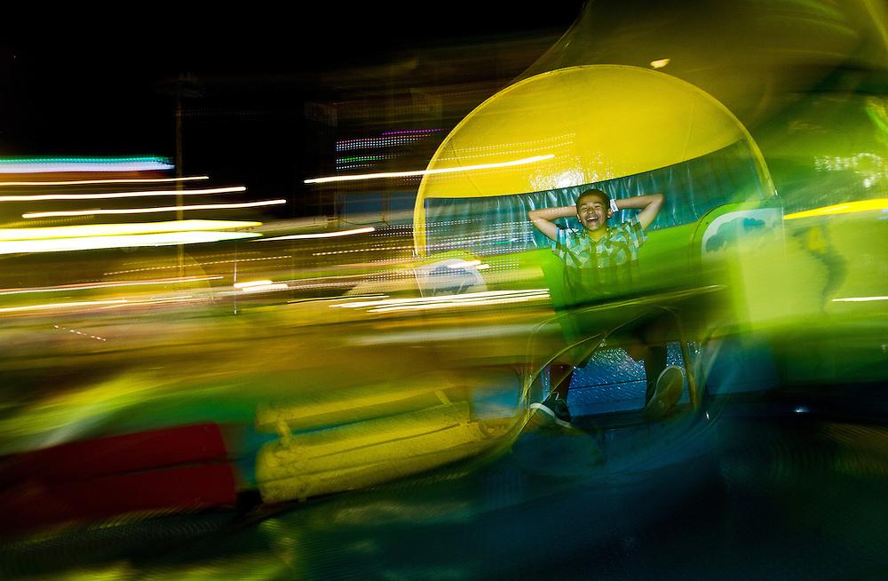 Fernando Alvaro, 13, of Grand Island has fun on a twister ride Friday night in the Midway at the Nebraska State Fair in Grand Island. (Independent/Matt Dixon)