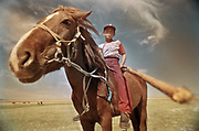 A young boy on horseback carrying a long pole to herd his livestock.