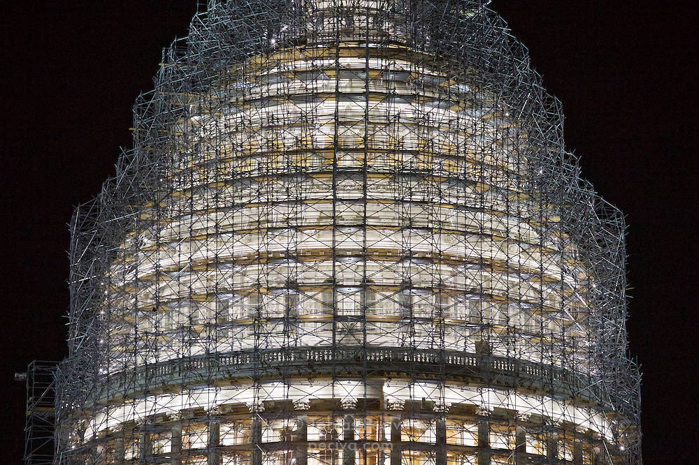 Nighttime view of the dome of the United States Capitol, with scaffolding in place for restoration work.