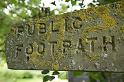 Lichen covered public footpath sign in the English countryside near Hatfield Peverel, England, United Kingdom.