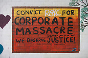 A mural prtesting about corporate housing policies that led to the Grenfell fire on the first anniversary of the tower block disaster, on 14th June 2018, in London, England. 72 people died when the tower block in the borough of Kensington & Chelsea were killed in what has been called the largest fire since WW2. The 24-storey Grenfell Tower block of public housing flats in North Kensington, West London, United Kingdom. It caused 72 deaths, out of the 293 people in the building, including 2 who escaped and died in hospital. Over 70 were injured and left traumatised. A 72-second national silence was held at midday, also observed across the country, including at government buildings, Parliament.