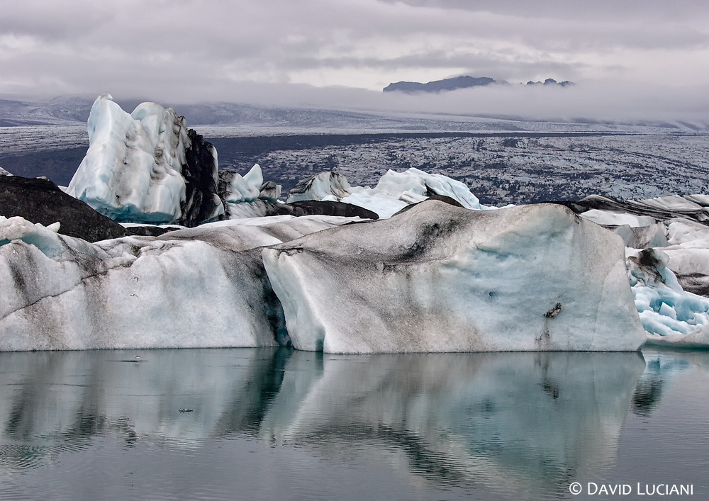 """According to """"Wikipedia"""" - Jökulsárlón lake or lagoon, the Icelandic """"glacier lake"""" is now reported to have doubled in size in the recent 15-year period. The huge blocks of ice that calve from the edge of Vatnajökull are about 30 metres (98 ft) high which fills the lagoon stocked with icebergs. Some icebergs appear naturally sculpted on account volcanic ashes from ancient eruptions that partly cover them. <br /> With the rate at which Vatnajökull is retreating and the lagoon is getting formed, in the near future, it is anticipated that there is likely to be a deep fjord where Vatnajökull is now. This retreat is also posing a threat to the National Highway Route 1 of Iceland. Reykjavík, the capital of Iceland is 250 kilometres (160 mi) from the lake and the road between the capital and the lagoon winds through a dozen other glaciers, which are also under retreat."""