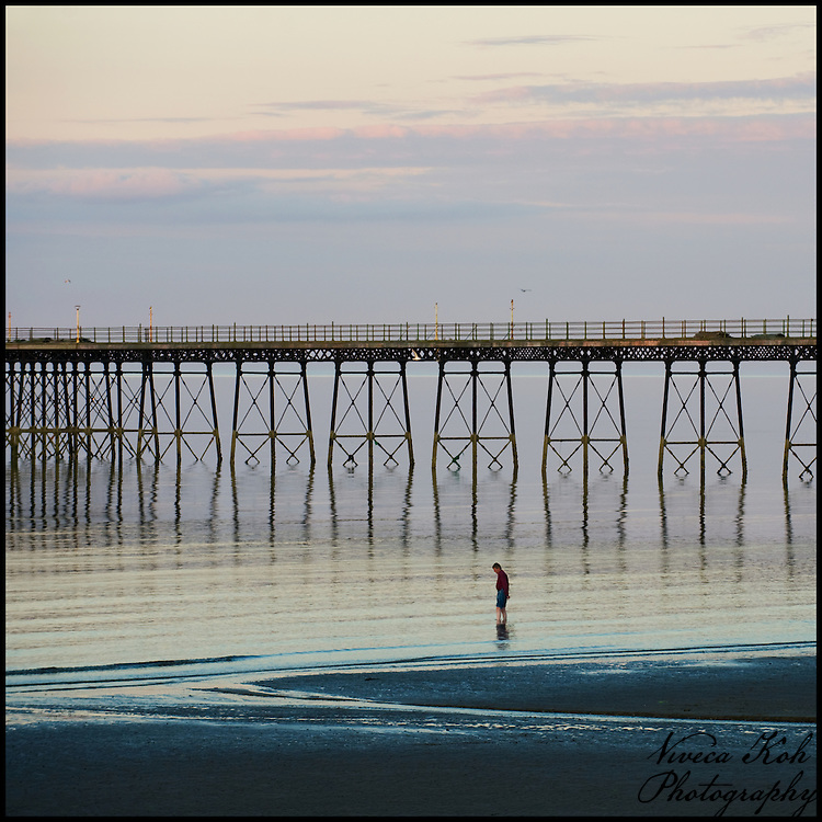Man paddling in the sea at sunset