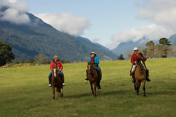 Chile, Lake Country: People riding horses at Peulla in a meadow in the Andes..Photo #: ch610-33257..Photo copyright Lee Foster www.fostertravel.com, lee@fostertravel.com, 510-549-2202.