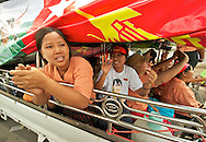 A truck decorated and packed with euphoric people singing and dancing, march on the streets. Myanmar, 2012.