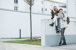 Young couple using digital tablet, Munich, Bavaria, Germany