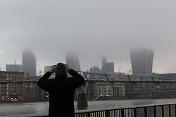 © Licensed to London News Pictures. 07/01/2017. LONDON, UK.  A man on the south bank takes a photograph of skyscrapers shrouded in mist and fog this morning. The weather in London today is misty, foggy and much milder than it has been during the past week.  Photo credit: Vickie Flores/LNP