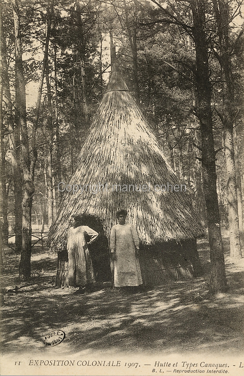 Kanak women from New Caledonia outside a traditional thatched hut, at the Colonial Exhibition of 1907, held in the Jardin d'Agronomie Tropicale, or Garden of Tropical Agronomy, in the Bois de Vincennes in the 12th arrondissement of Paris, postcard from the nearby Musee de Nogent sur Marne, France. The garden was first established in 1899 to conduct agronomical experiments on plants of French colonies. In 1907 it was the site of the Colonial Exhibition and many pavilions were built or relocated here. The garden has since become neglected and many structures overgrown, damaged or destroyed, with most of the tropical vegetation disappeared. The site is listed as a historic monument. Picture by Manuel Cohen / Musee de Nogent sur Marne