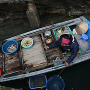 Local sellers try to sell their goods to tourist boats in Ha Long Bay, Vietnam. The bay consists of a dense cluster of 1,969 limestone monolithic islands. Ha Long Bay, is a UNESCO World Heritage Site, and a popular tourist destination. Ha Long, Bay, Vietnam. 11th March 2012. Photo Tim Clayton