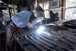 Blacksmith fusing garden gate in workshop, Bavaria, Germany