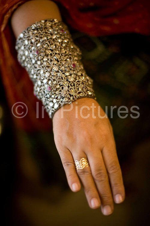 A woman holds a jewel encrusted bracelet with precious stones at the Gem Palace, Jaipur's foremost jewellers, Jaipur, India