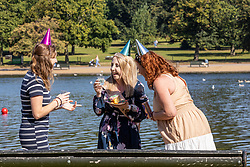 Licensed to London News Pictures. 16/09/2021. London, UK. Friends celebrate a birthday as they enjoy the late summer sun in Hyde Park, London as weather forcasters predict a warmer few days ahead with highs of 24c for London and the South East. Photo credit: Alex Lentati/LNP