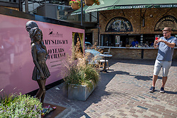 © Licensed to London News Pictures. 23/07/2021. LONDON, UK.  A man views the statue of Amy Winehouse by sculptor Scott Eaton in Stables Market in Camden Town on the tenth anniversary of the late singer's death.  Photo credit: Stephen Chung/LNP