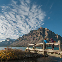 Dramatic clouds soar over hikers crossing a bridge beside Bow Lake in Banff National Park, Alberta, Canada.  Behind is Crowfoot Mountain.