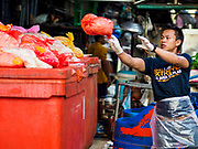 "04 DECEMBER 2018 - BANGKOK, THAILAND:  A worker sorts meat products wrapped in plastic bags in Khlong Toei market. The issue of plastic waste became a public one in early June when a whale in Thai waters died after ingesting 18 pounds of plastic. In a recent report, Ocean Conservancy claimed that Thailand, China, Indonesia, the Philippines, and Vietnam were responsible for as much as 60 percent of the plastic waste in the world's oceans. Khlong Toey (also called Khlong Toei) Market is one of the largest ""wet markets"" in Thailand. December 4 was supposed to be a plastic free day in Bangkok but many market venders continued to use plastic.    PHOTO BY JACK KURTZ"
