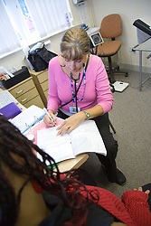 Midwife in consultation and taking notes with her patient,