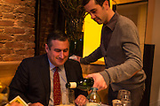 New York, NY, Sept. 30, 2013. Grant Reynolds, wine director at Charlie Bird, serving wine to diner Juan Ruiz.
