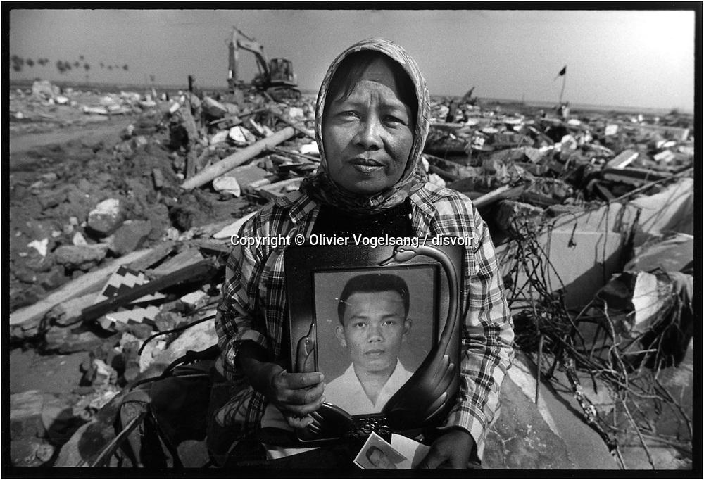 Indonésie. Banda Aceh. Etat des lieux sur l'ile de Sumatra 3 mois après le tsunami du 26 décembre 2004. Nurela AB tient la photo de son fils de 20 ans disparu Rio pirma Sanyaya. Ils viennent de Kajhu Indah. 2000 habitants avant, aujourd'hui 180. Le trax en arrière fond déblaie les restes de sa maison sous le regard du père yusril sah. <br /> <br /> <br /> <br /> Indonesia. Banda Aceh. Report on the island of Sumatra 3 months after the tsunami of december 26, 2004.  This woman holds a photo of her twenty years old son who disappeared.