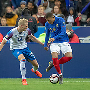 PARIS, FRANCE - March 25:  Kylian Mbappé #10 of France teases Hordur Bjorgvin Magnusson #18 of Iceland during the France V Iceland, 2020 European Championship Qualifying, Group Stage at  Stade de France on March 25th 2019 in Paris, France (Photo by Tim Clayton/Corbis via Getty Images)