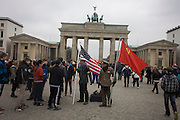 Actors in US and Soviet army uniforms hold flags to recount German history during the second world war and later, the cold war - beneath the Brandenburg Gate in Unter den Linden in central Berlin, Germany.