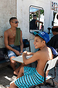 Two 2 Brazilian youths sitting down on chairs in the street at young independent barber shop hair stylist in the street for the young people guys of Vila Valquiere, West Zone Zona Oueste, Rio de Janeiro