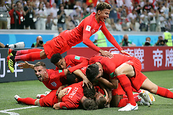 England's Harry Kane (hidden) is mobbed by team-mates as he scores his side's first goal of the game during the FIFA World Cup Group G match at The Volgograd Arena, Volgograd.