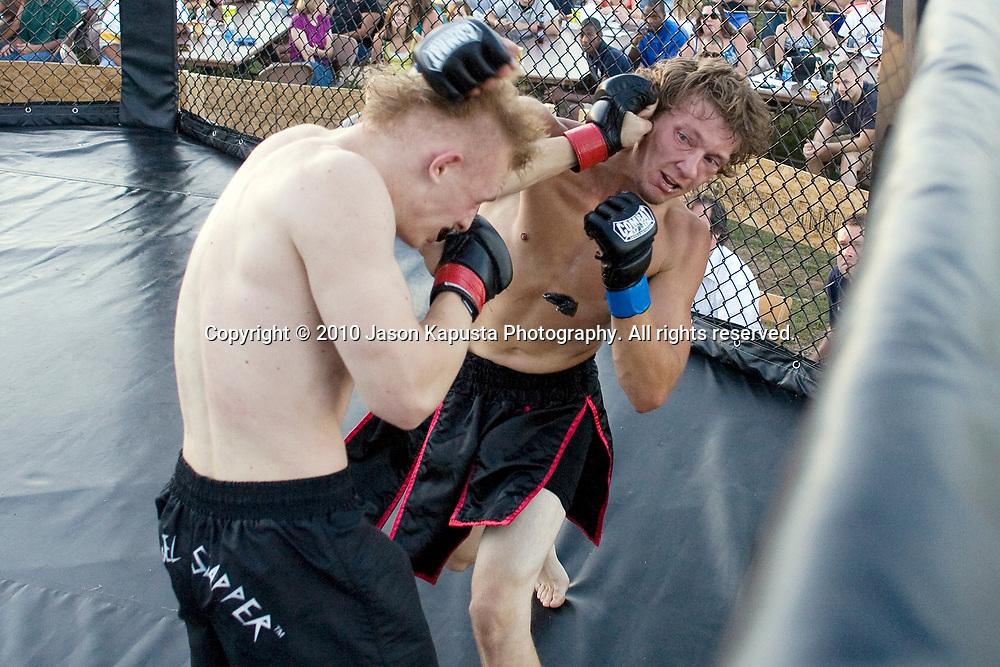 Chris Layten lands a punch to the head of John Onyshko, knocking out his mouth piece, at Yankee Lake Brawlroom 22 on Saturday, April 7, 2010 in Yankee Lake, Ohio.