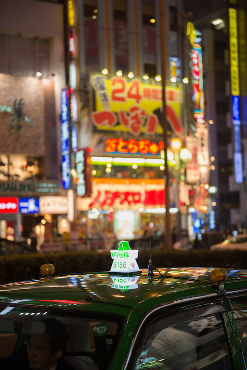 Detail of a taxi at night in the Shinjuku district of Tokyo.